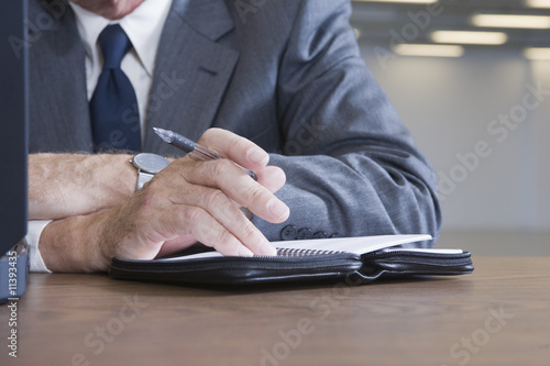 Businessman writing in his notebook