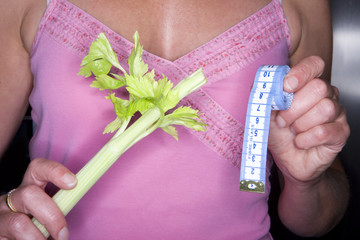 Close up of woman holding celery and tape measure