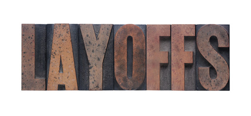 the word 'layoffs' in old ink-stained wood type