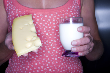 Close up of woman holding cheese and glass of milk