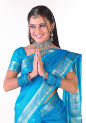 Smiling teenage girl in sari with welcome expression