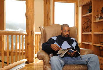 African American Male Reading a  Magazine