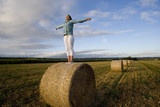 Teenage girl (16-18) standing on bale of hay in field with arms outstretched
