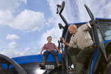 Farmer and grandson sitting on tractor