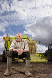 Portrait of farmer sitting on machinery with straw bale