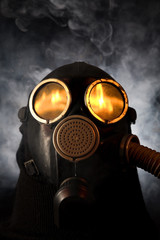 Man in gas mask over smoky background