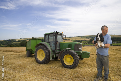 Farmer holding dog in front of tractor in barley field
