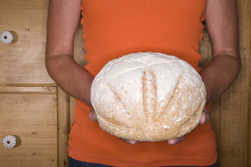 Close up of woman holding loaf of bread