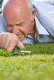 Close up of senior man cutting grass with scissors
