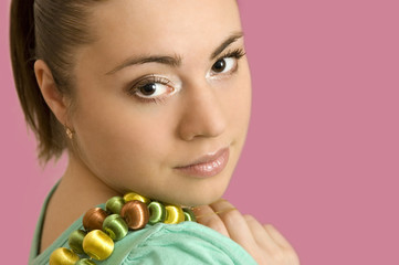 The beautiful young woman with a beads on a pink background