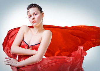 Young beautiful woman in corset with red cloth