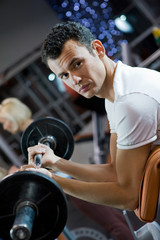 Handsome young man lifting weight in a gym