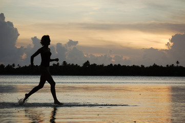 Young woman runner, jogging in water, Bora French Polynesia