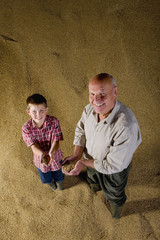 Farmer and grandson holding grains on grain heap