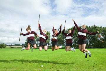 Teenage girl hockey team jumping on field