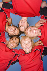 Portrait of smiling teenage girls hugging in sports uniforms