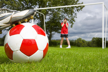 Close up of soccer player aiming ball at frightened goalie