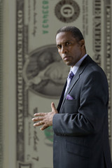 Serious businessman standing in front of large one hundred dollar bill