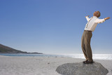 Businessman standing on beach with arms outstretched