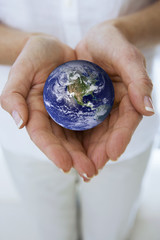 Close up of womans hands cupping miniature globe