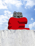 House weighing down British pound symbol on edge of cliff