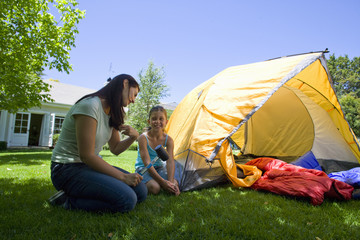 Mother and daughter setting up tent in backyard