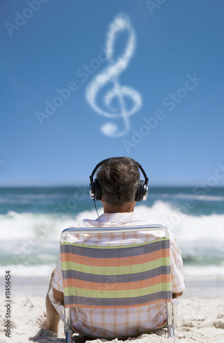 Man listening to headphones on beach with clef cloud overhead