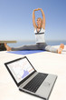 Woman stretching on mat with financial figures on laptop  in foreground