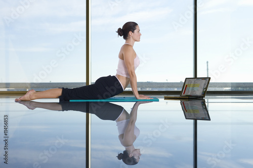Woman doing yoga next to laptop