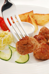 Fried meatballs with chips and vegetable salad