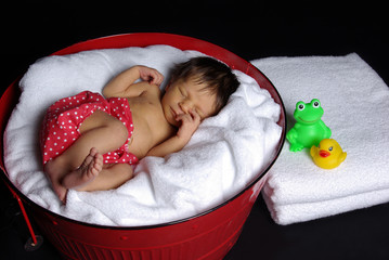 Newborn baby slepping in red tub