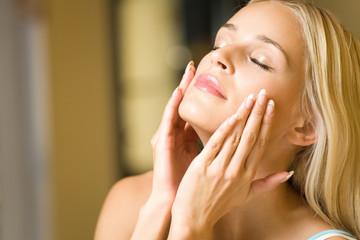 Portrait of young happy woman applying facial cream