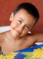 Bambino a tavola con la bocca sporca di sugo