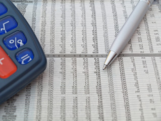Stock quotes with pen and calculator