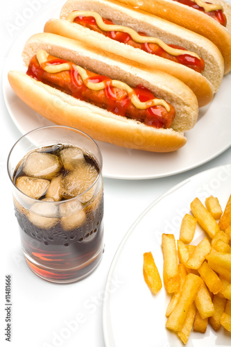 a glass of cola with ice, french fries and three classic hotdogs