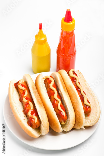 three classic hotdogs with ketchup and mustard bottles