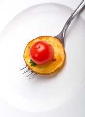 crispy roasted potato on a fork with cherry tomato on top