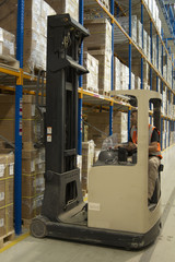 Warehouse worker picking stock wth reach truck