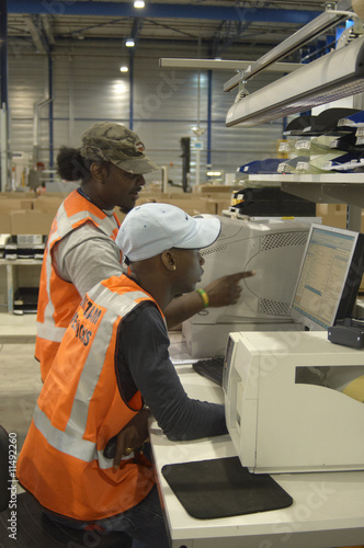 Warehouse operatives checking computer