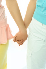two women hold hands
