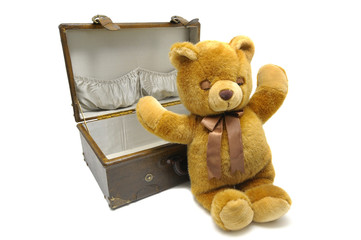 Old case with teddy bear isolated against a white background