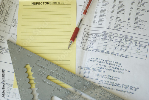 Inspection notes, ruler, and red pen atop construction plans