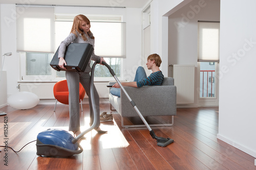 Woman vacuum cleaning man watching tv