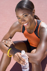 Young female athlete with bottle of water, smiling, portrait, elevated view