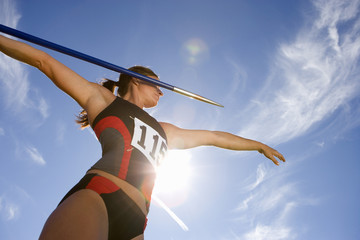 Female athlete preparing to throw javelin, low angle view (lens flare)