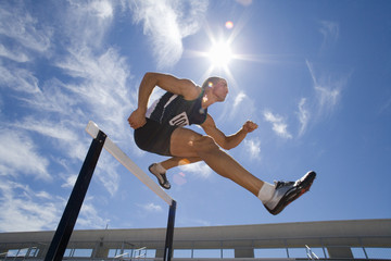 Male athlete jumping over hurdle, low angle view (lens flare)