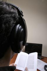 Homem ouvindo música a lendo à frente do computador