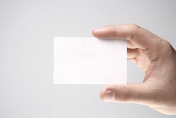 Mão segurando um cartão pessoal branco