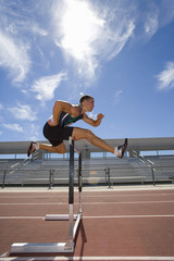 Male athlete jumping over hurdle, side view (lens flare)
