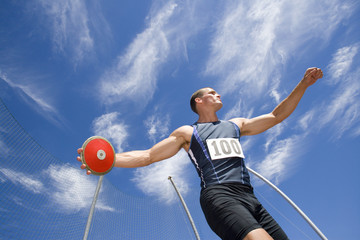 Male athlete with discus, low angle view